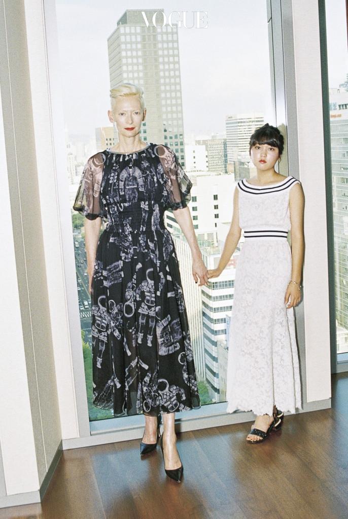틸다 스윈튼이 입은 우주복 프린트 시어 드레스, 검은색 스틸레토 힐, 안서현이 입은 스트라이프 네크라인의 흰색 레이스 소재 원피스, 스트랩 샌들, 왼팔의 참 장식 브레이슬릿은 샤넬(Chanel).