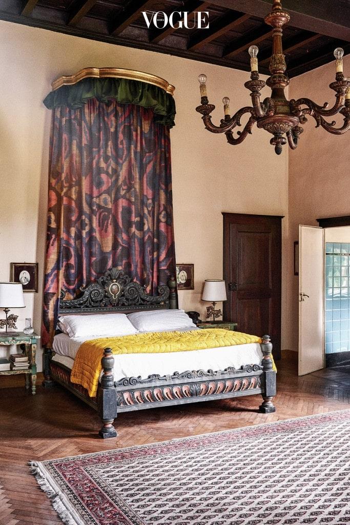 침실 내부는 어두운 색의 목재와 앤티크 가구로 꾸몄다. 침대 뒤의 컬러풀한 바틱 패턴 커튼은 데다르사 제품.