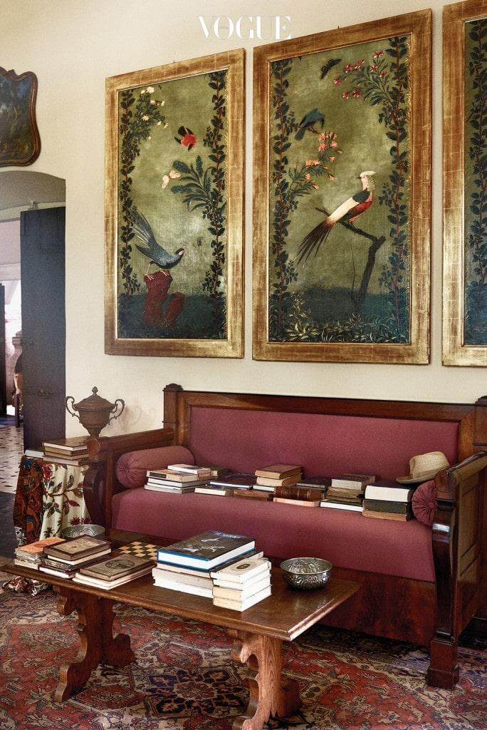 19세기 장식 패널 아래 제국주의 시대 소파 위에는 잊혀진 듯한 오래된 책들이 모여 있다.