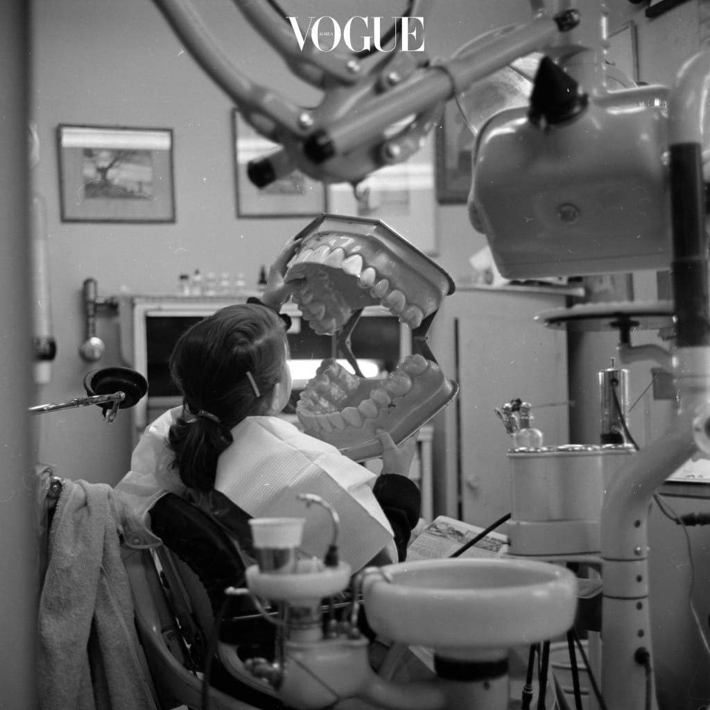 A young patient in the dentist's chair holding a giant model of a set of dentures which the dental hygienist uses to demonstrate proper brushing techniques.   (Photo by Orlando/Getty Images)