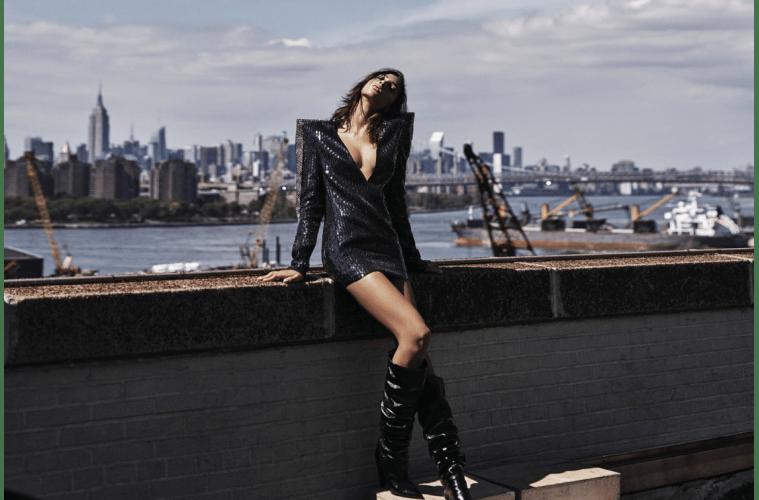 어깨를 강조한 브이넥 미니 드레스와 느슨한 싸이하이 부츠가 뉴욕의 마천루가 보이는 공간과 어우러져 더욱 매혹적으로 다가온다. 화보 속 모든 의상과 신발, 가방과 액세서리는 생로랑 바이 안토니 바카렐로(Saint Laurent by Anthony Vaccarello).