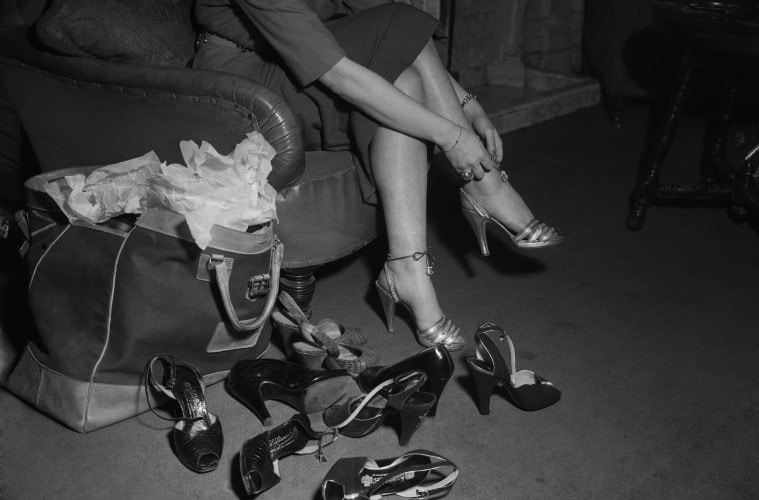 A woman trying on a selection of shoes, 1951. (Photo by Hulton Archive/Getty Images)