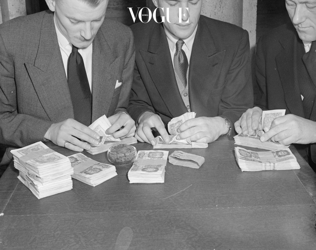 6th February 1952:  Businessmen counting banknotes.  (Photo by Harold Clements/Express/Getty Images)