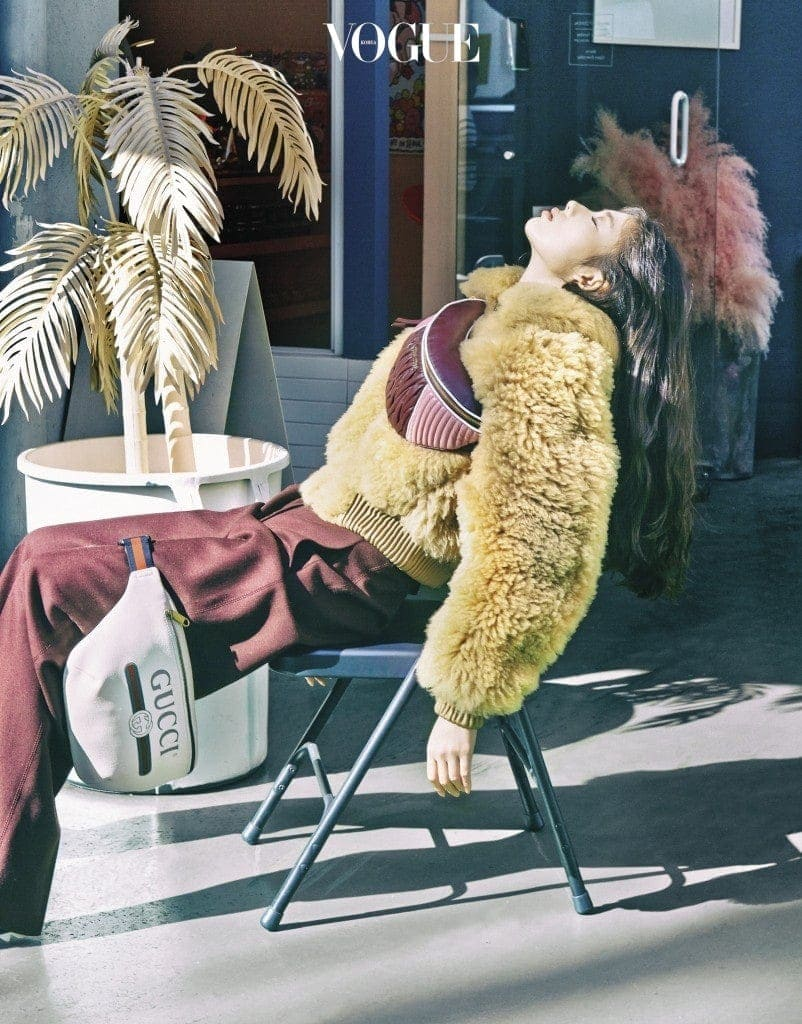 복슬복슬한 양털 아우터는 아크네 스튜디오(Acne Studios), 버건디색 팬츠는 스텔라 맥카트니(Stella McCartney), 상체에 멘 힙색은 미우미우(Miu Miu), 흰색 로고 힙색은 구찌(Gucci).