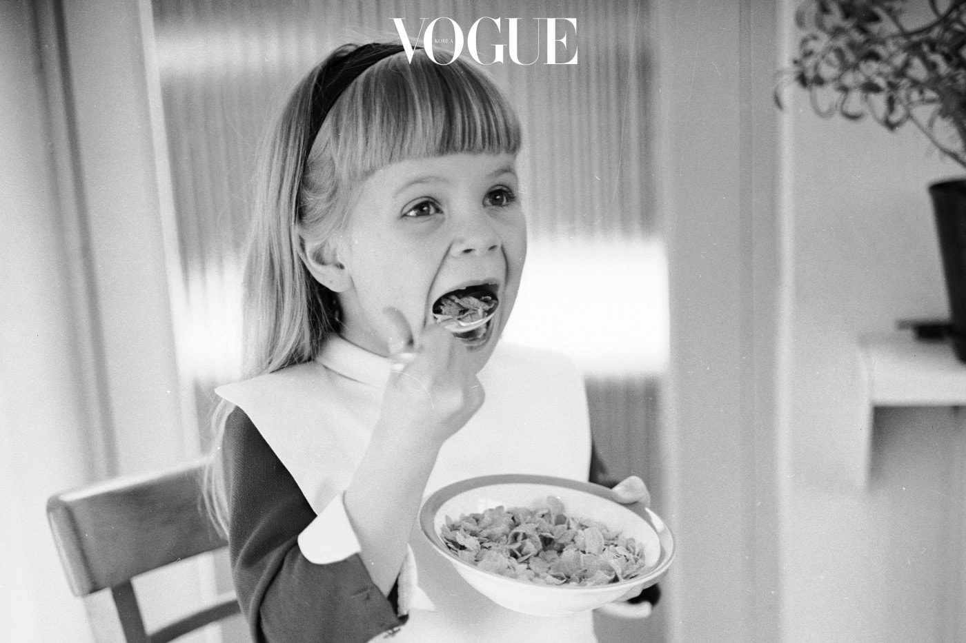 12th April 1966:  A little girl wears a pretty bib in order to eat a bowl of cereal without spillage.  (Photo by Chaloner Woods/Getty Images)