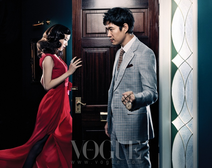 밝은 회색 체크무늬 수트와 셔츠는 모두 권오수 클래식(Kwonohsoo Classic), 타이는 갈라테오(Galateo), 포켓치프는 라피규라(La Figura), 회중시계는 벨앤누보(Bell&Nouveau).문 앞에 선 여자의 붉은색 드레스는 베라 왕(Vera Wang), 볼드한 실버 반지는 블랙뮤즈(Blackmuse)와 벨앤누보.