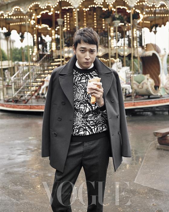 추상적인 패턴의 니트 스웨터와 잔잔한 핀스트라이프 팬츠에 큼직한 라펠의 피 코트를 어깨에 걸쳤다.