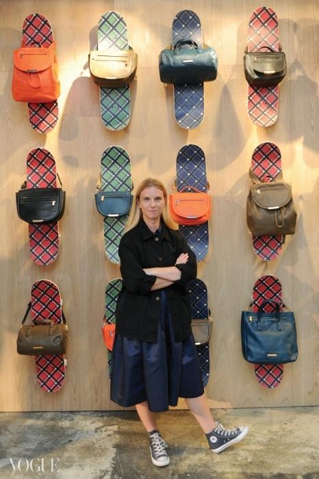 알록달록한 체크 패턴스케이트 보드와 함께 선보인신상 가방들 앞에서포즈를 취한 케이티 힐리어.