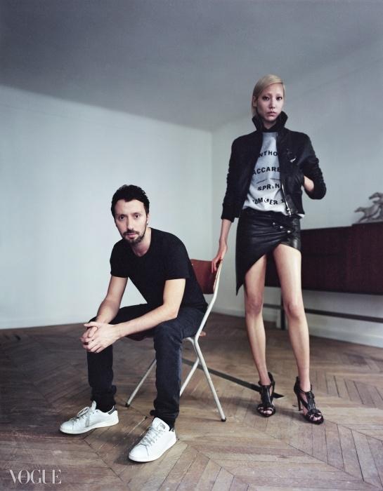 검정 티셔츠와 데님진, 스니커즈까지,늘 자신만의 시그니처 룩을 고집하는안토니 바카렐로가 2015 봄 컬렉션 오프닝 룩을입은 모델 수주와 함께 포즈를 취했다.