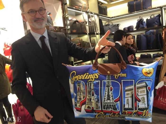 롱샴의 CEO인 장 카세그랭이 샹젤리제 매장 오픈을 기념해 특별히 만들어진 제레미 스캇의 파리 포스트카드 백(Paris Postcard bag) 한정판을 들고 있다.