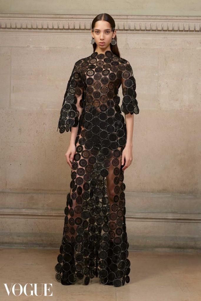 오간자와 수작업으로 이루어진 기하학적 모티프의 메탈 링으로 장식된 비대칭 드레스를 입은 야스민 바이날둠.