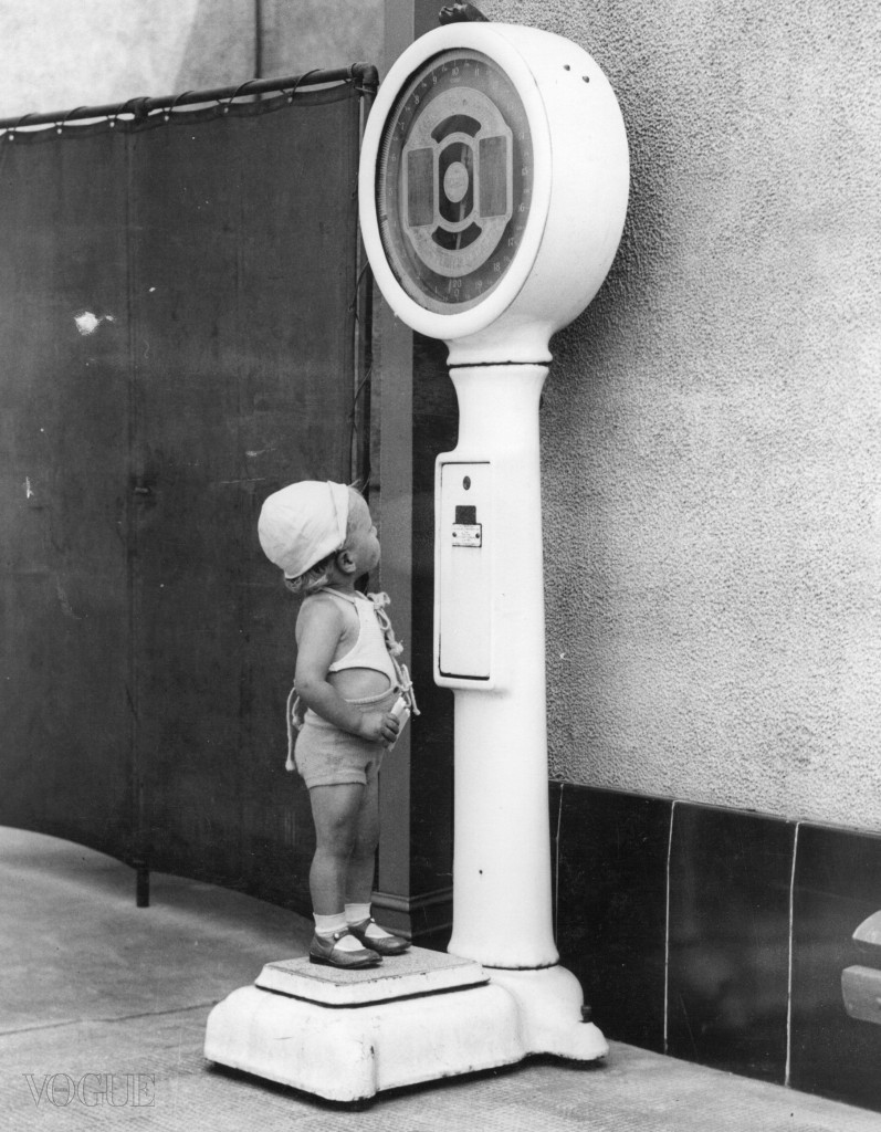 7th August 1937:  A fat conscious toddler on hodiday has her weight checked on a weighing machine.  (Photo by Fox Photos/Getty Images)