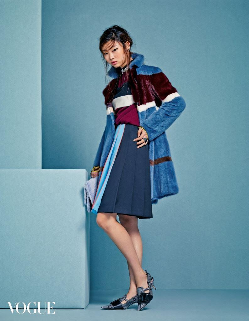 버건디, 블루, 브라운, 화이트 컬러가 믹스된 밍크 코트는 발렌티노(Valentino), 니트 톱과 플리츠 스커트는 프라다(Prada), 체인 목걸이는 생로랑(Saint Laurent), 블랙 스터드 귀고리와 왼손 반지는 지방시(Givenchy), 오른손 포 핑거 링은 디올(Dior), 모피 클러치는 프로엔자 스쿨러(Proenza Schouler), 슬링백은 미우미우(Miu Miu).