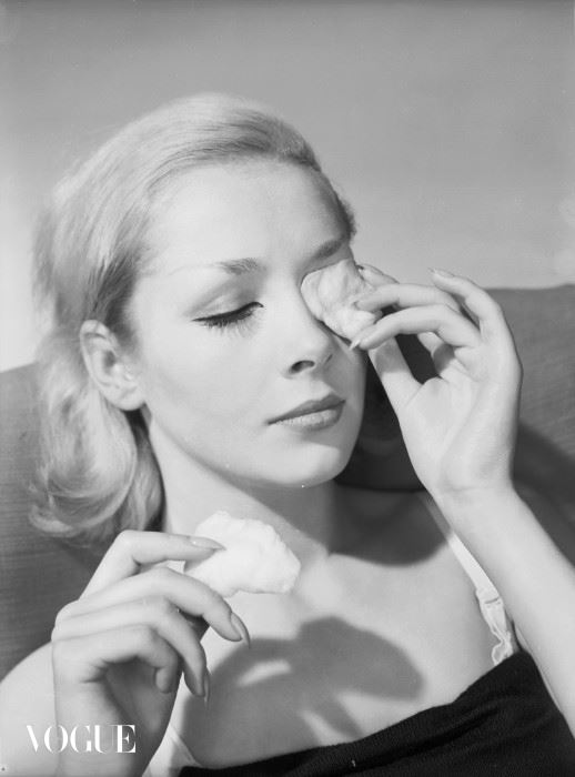10th November 1960:  A model applies pads of cotton wool, soaked in lotion, to the eyes.  (Photo by Chaloner Woods/Getty Images)