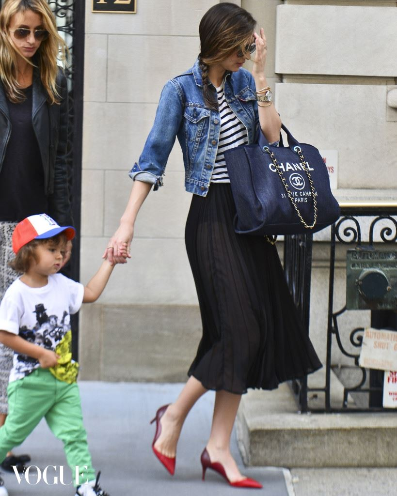Miranda Kerr out and about with Flynn Bloom wearing a jean jacket, see through skirt and carrying a Chanel tote in New York City