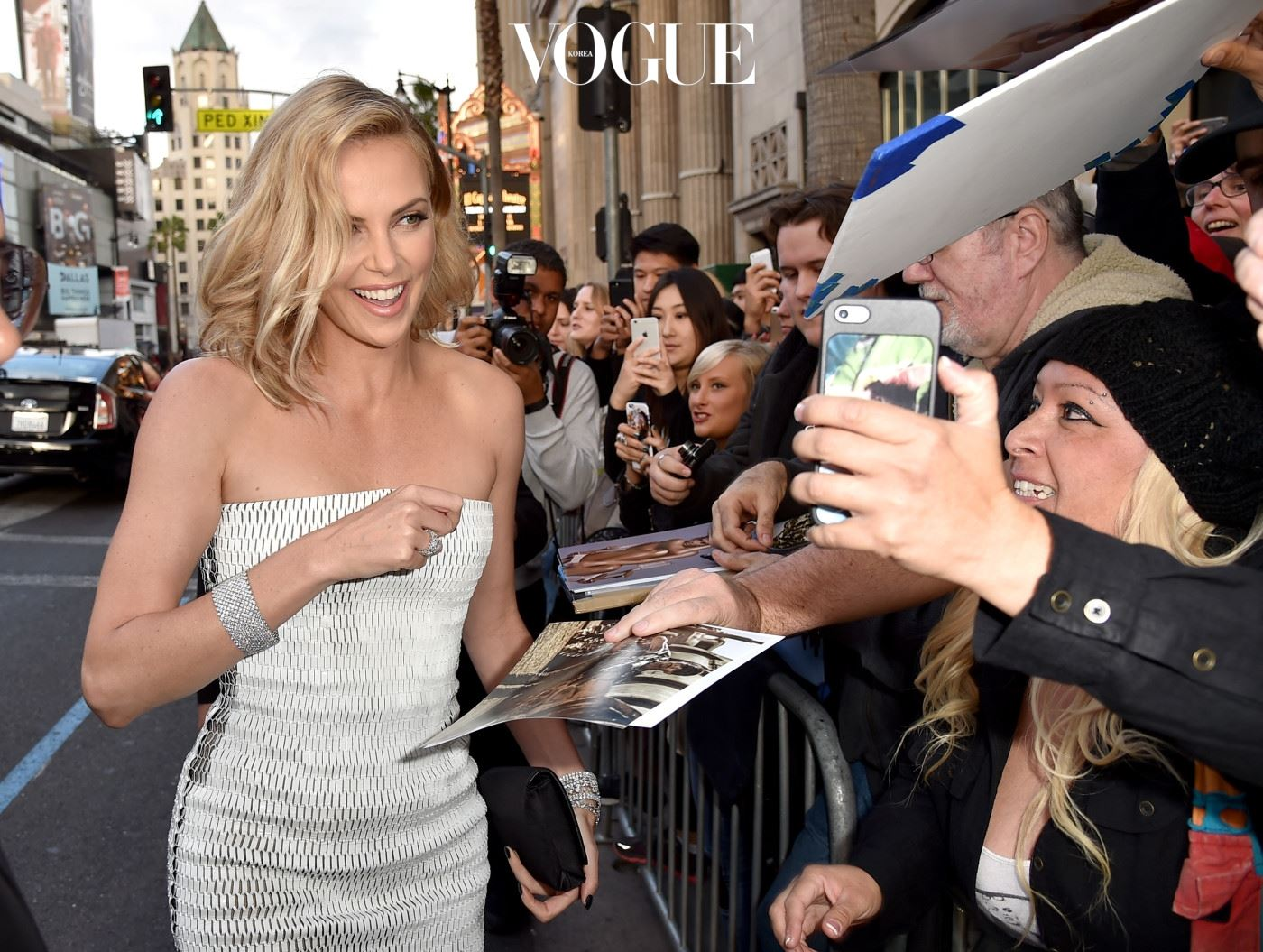 """HOLLYWOOD, CA - MAY 07:  Actress Charlize Theron signs autographs as she attends the premiere of Warner Bros. Pictures' """"Mad Max: Fury Road"""" at TCL Chinese Theatre on May 7, 2015 in Hollywood, California.  (Photo by Kevin Winter/Getty Images)"""
