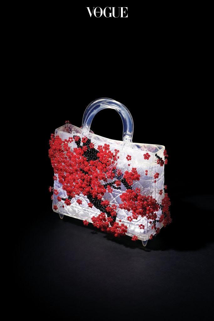 """사라지는 것들의 아름다움HWANG RAN 매화 는 1997년 뉴욕에서 활동하기 시작한 이래 황란 작품의 감성을 대표하 는 모티브다. """"벚꽃은 화려하기만 하지만 매화는 담백해요. 가지가 탁탁 꺾이고 꽃도 벚꽃만큼 많이 피지 않지요. 그 고요하고 은은한 정취가 한 국인의 정서, 정신과 잘 맞아떨어지기 때문에 사군자 중 하나로 꼽혔을 거예요."""" 황란이 꽃 피운 현대판 매화는 투명한 형태의 레이디 디올에 내 려앉아 고아한 자태를 뽐낸다."""
