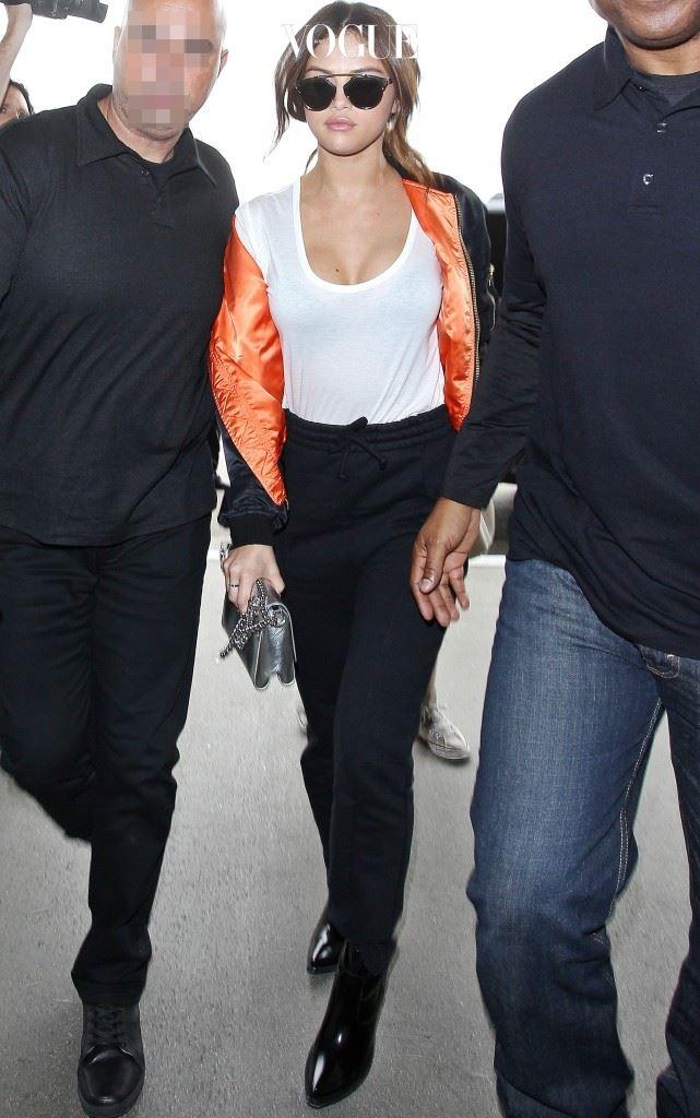 화이트 티셔츠와 검정 팬츠, 주황색 안감이 시선을 사로잡는 보머 재킷의 에지 시크 룩.
