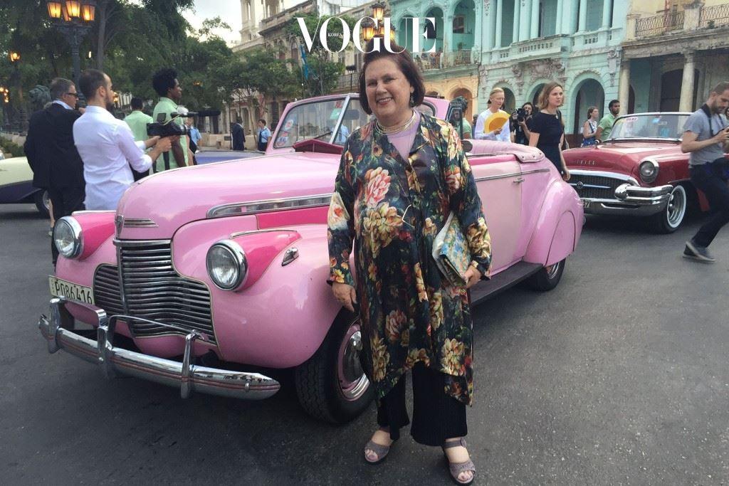 수지가 버블껌 분홍색 시보레 자동차 앞에서 포즈를 취했다.