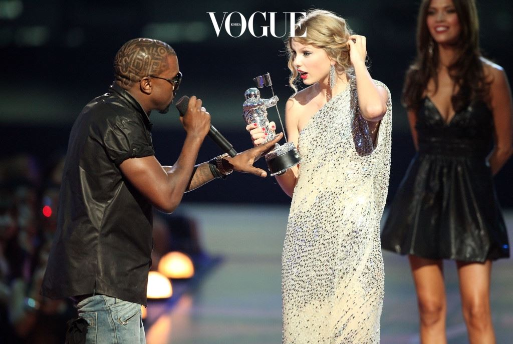 """NEW YORK - SEPTEMBER 13:   Kanye West (L) jumps onstage after Taylor Swift (C) won the """"Best Female Video"""" award during the 2009 MTV Video Music Awards at Radio City Music Hall on September 13, 2009 in New York City.  (Photo by Christopher Polk/Getty Images)"""
