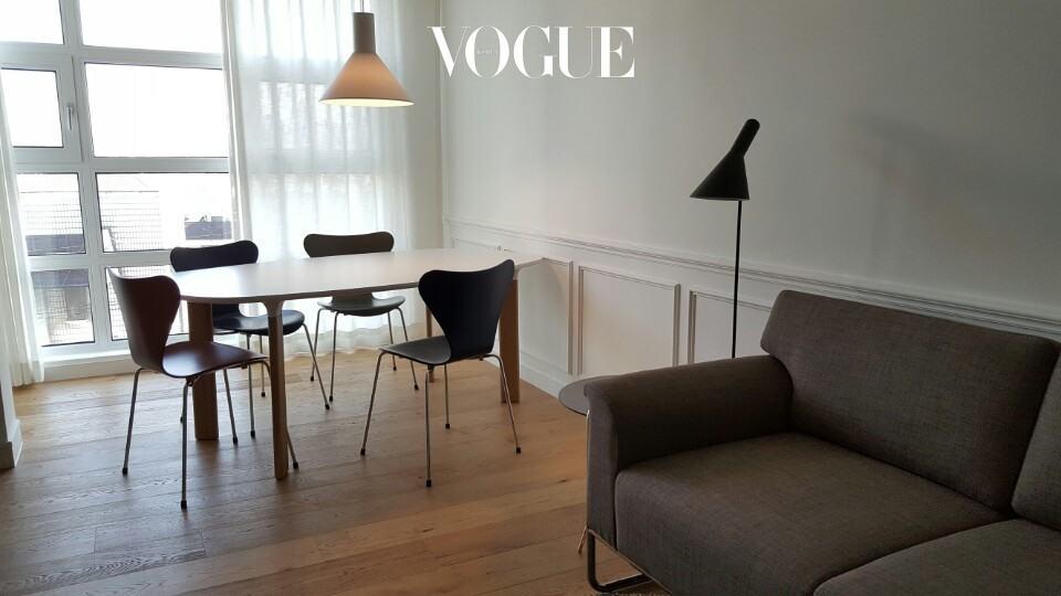 가족들이 편하게 쉴 수 있는 중간 거실 세팅. 식사를 하거나 일을 할 수 있도록 프리츠 한센(Fritz Hansen)의 나무 테이블과 그레이ᆞ네이비ᆞ브라운톤의 의자, 그리고 편안한 패브릭 소파를 함께 어울렸다.