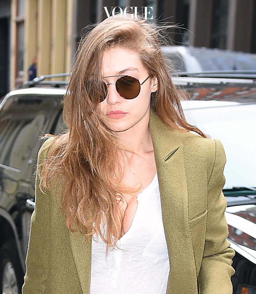 """Gigi Hadid shows off her ample assets as she steps out in a low cut white tee, ripped jeans and camo trench coat for a meeting at the """"V Magazine"""" in SoHo, New York City Pictured: Gigi Hadid  Ref: SPL1429673  270117   Picture by: Splash News Splash News and Pictures Los Angeles:310-821-2666 New York:212-619-2666 London:870-934-2666 photodesk@splashnews.com"""