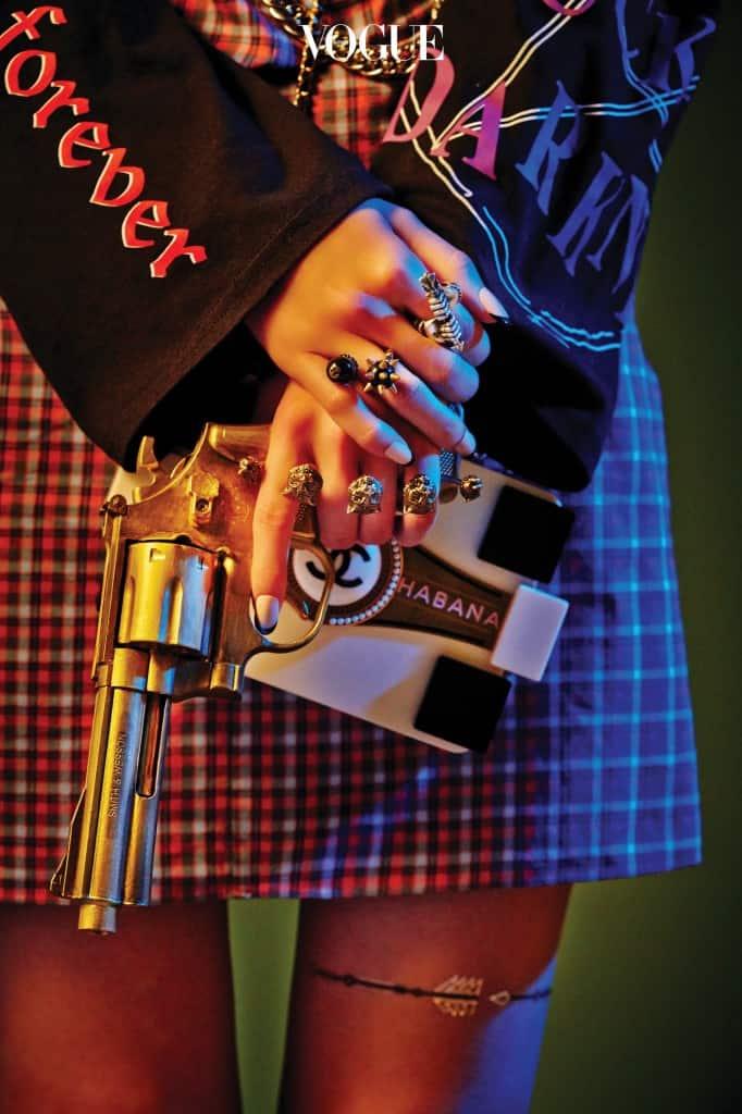 체인이 달린 체크 패턴 원피스는 베트멍 (Vetements at 10 Corso Como), 스파이크 장식 반지, 활모양 은색 반지, 호랑이 장식 너클링은 구찌 (Gucci), 미니 박스 백은 샤넬(Chanel).