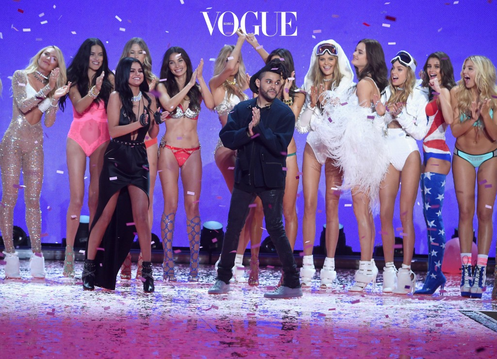 """NEW YORK, NY - NOVEMBER 10:    (Back Row L-R) Models Candice Swanepoel, Adriana Lima, Behati Prinsloo, Lily Aldridge, Romee Strijd, Alessandra Ambrosio,  Monica """"Jac"""" Jagaciak, Kate Grigorieva, Stella Maxwell, Taylor Hill, Rachel Hilbert, (front row L-R) Singer Selena Gomez, and Singer The Weeknd walk the runway during the 2015 Victoria's Secret Fashion Show at Lexington Avenue Armory on November 10, 2015 in New York City.  (Photo by Jamie McCarthy/Getty Images)"""