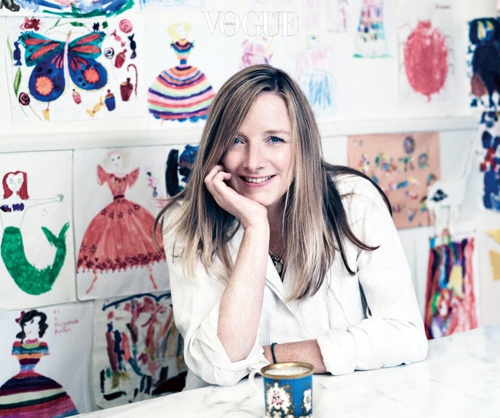 사라 버튼의 등 뒤로 그녀의 두 딸이 그린 그림이 벽을 가득 채우고 있다.