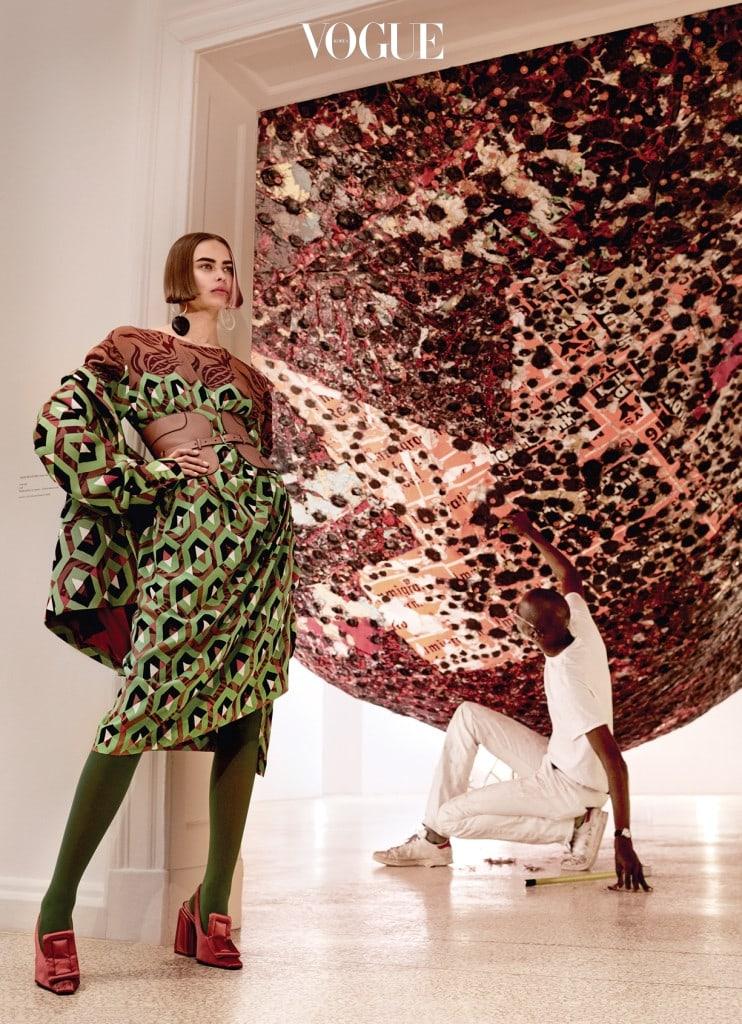 CULTURE CLASH 테라코타 색이 섞인 기하학적 패턴의 드레스는 마크 브래드포드의 'Spoiled Foot' 작품 앞에서 완전히 두드러진다. 재킷과 드레스는 드리스 반 노튼(Dries Van Noten), 귀고리는 시몬 밀러(Simon Miller), 벨트는 토즈(Tod's), 초록색 타이츠는 팔케(Falke), 구두는 마르니(Marni).