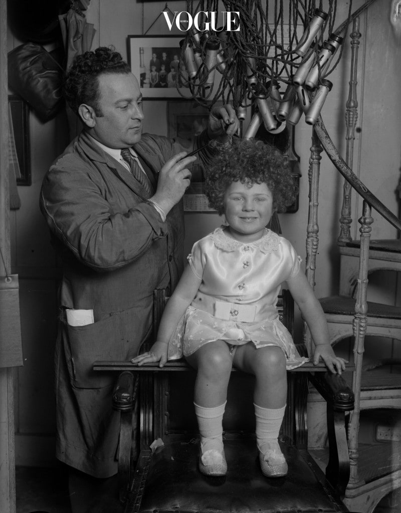 17th March 1930:  Hairdresser M. Balbus removes the electric curlers from little Peggy Vaff's hair after giving her a bubble perm.  (Photo by Fox Photos/Getty Images)