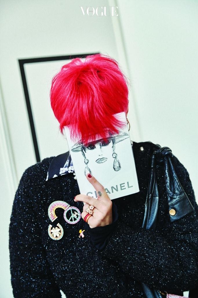 칼 라거펠트의 스케치가 그려진 샤넬의 2018 S/S 컬렉션 초대장을 든 권지용. 손톱에 바른 네일 컬러는 물론이고 여성복, 샤넬 브로치와 반지도 그가 걸치면 지극히 권지용답다.