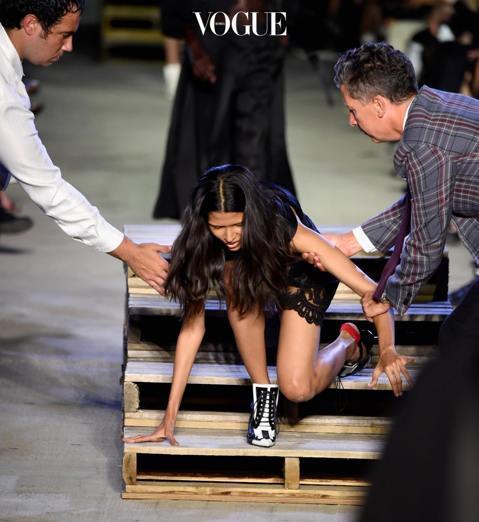 NEW YORK, NY - SEPTEMBER 11:  Model Pooja Mor wearing Givenchy Spring 2016 stumbles and falls on the runway during New York Fashion Week at Pier 26 at Hudson River Park on September 11, 2015 in New York City. Stefano Tonchi, Editor In Chief of W Magainze (right), helps Mor to her feet. (Photo by Frazer Harrison/Getty Images)