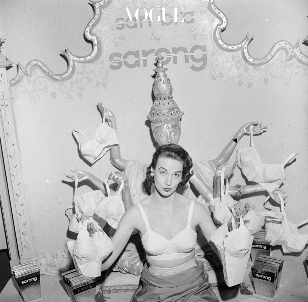 1949:  A woman modelling a 'Sarong' brand sari bra whilst holding one on in each of her outstretched hands. She is standing in front of an effigy of an multi-armed Hindu goddess toting a bra in each hand.  (Photo by Vecchio/Three Lions/Getty Images)