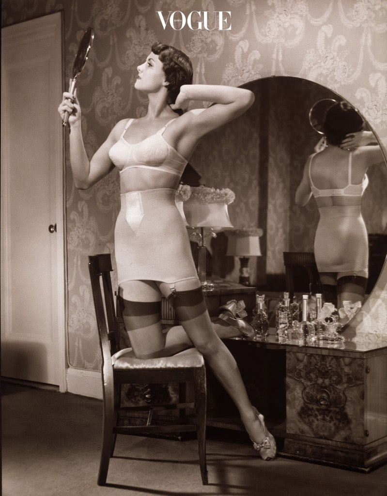 A woman kneels in a chair dressed in her brassiere and stockings, admiring herself in a hand mirror and arranging her hair, 1940s. (Photo by George Marks/Retrofile/Getty Images)