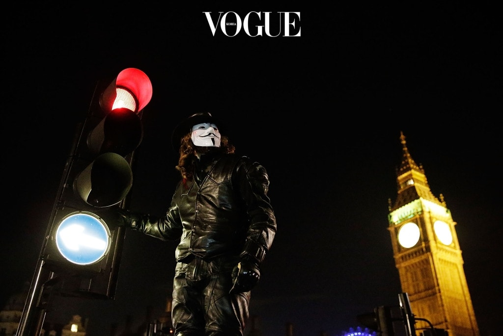 """LONDON, ENGLAND - NOVEMBER 05:  Members of the Anonymous group protest outside the Houses of Parliament on November 5, 2012 in London, England. The group wear masks inspired by a character from the film """"V for Vendetta"""", which culminates in the march en masse of the public against parliament, in protest against a authoritarian goverment, on the fifth of November.  (Photo by Matthew Lloyd/Getty Images)"""