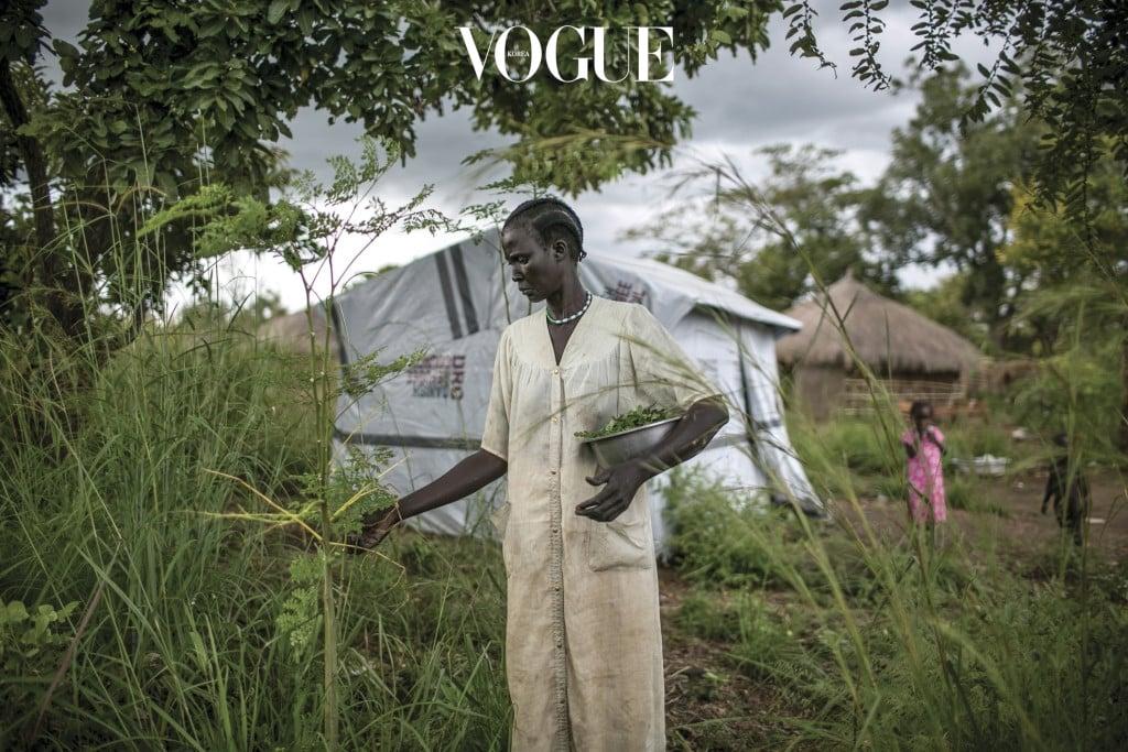니야각 콕이 우간다의 비디비디 난민 캠프 내 텐트 주변에 자란 풀잎을 뜯고 있다. 이 풀잎으로 음식을 만들어볼 생각이다. 니야각은 2016년 7월 주바에서 두 번째 큰 내전이 발생했을 당시 딩카족 군인 여섯 명으로부터 성폭행을 당했다.