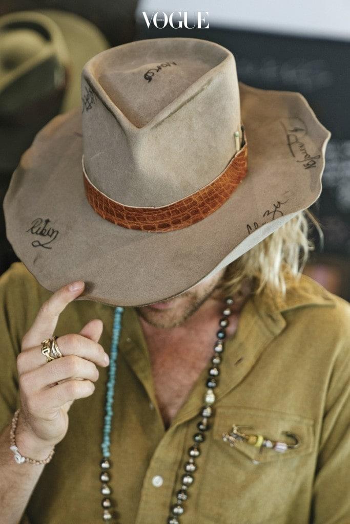 디자이너가 직접 모자를 쓰고 디테일을 설명하고 있다. 각종 레터링과 가죽 브림, 성냥 디테일이 돋보인다.